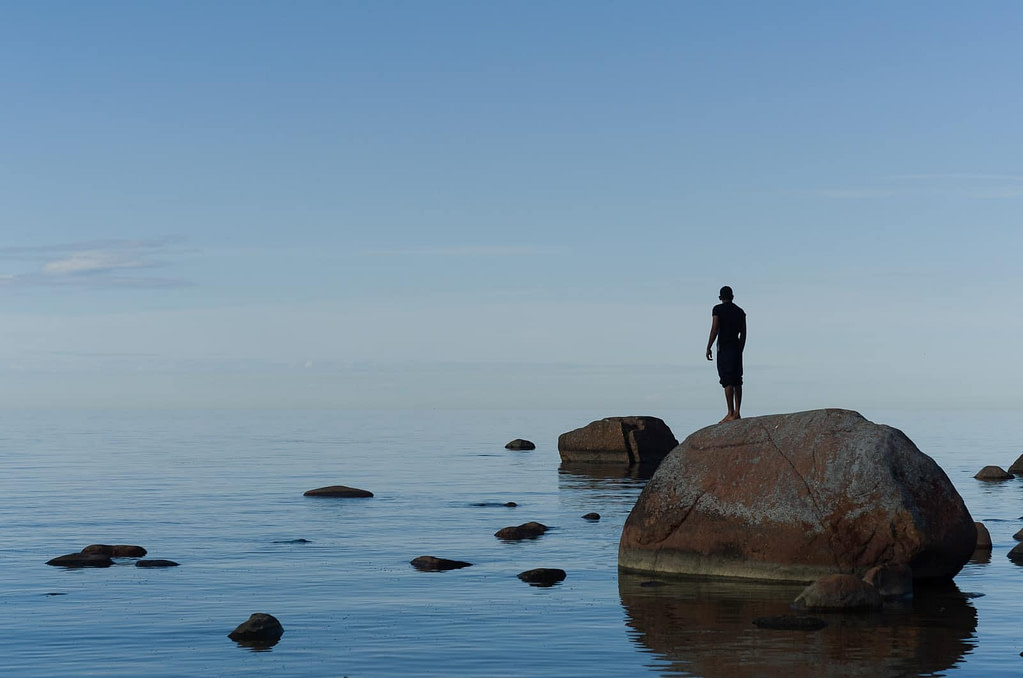 man standing on brown rock