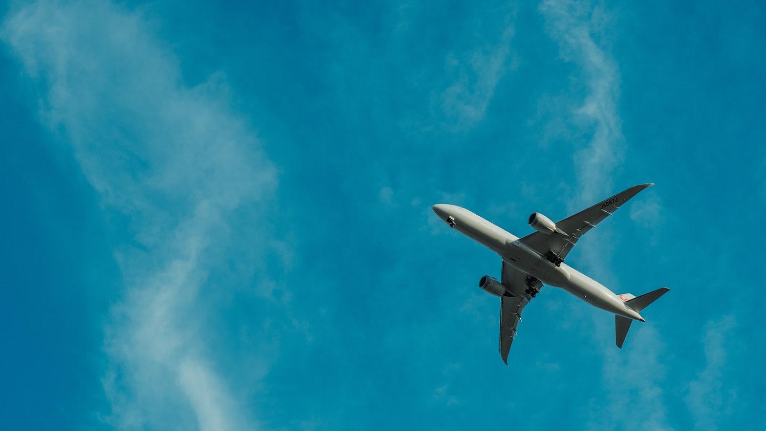 gray airplane flying during daytime